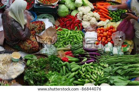 Old muslim woman selling fresh vegetables in traditional asian market. - stock photo
