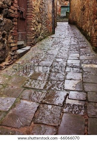 old narrow alley in tuscan village - antique lane with pavement of stone - tuscany, italy - stock photo