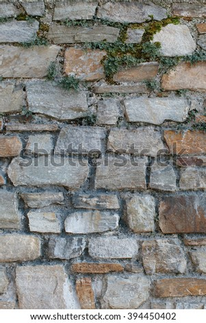 Old natural stone wall background texture with unevenly cut rectangular blocks in rows in shades of grey and brown with a rough surface