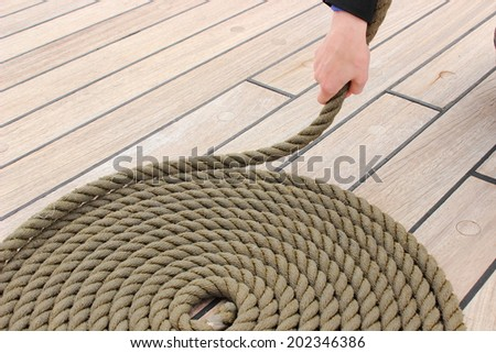 Old nautical thick rope wrapped in spiral lying on weathered deck of yacht, circle of thick rope with hand of woman - stock photo