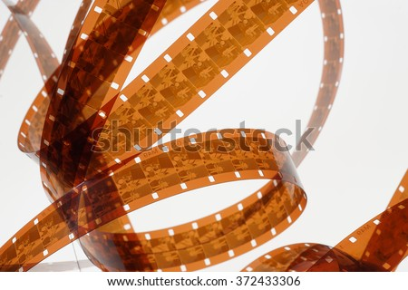 Old negative 16 mm film strip on white background, strip of tangled movie film - place for copy and space text - stock photo