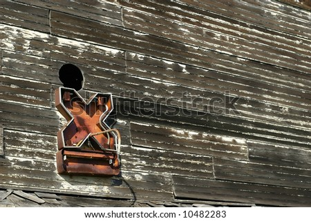 "old neon letter ""x"" attached to an outside wall of a building with peeling paint - stock photo"