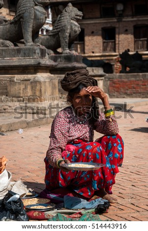 Old Nepalese woman selling corn for pigeons on Bhaktapur Durbar square, Nepal, October 10, 2012