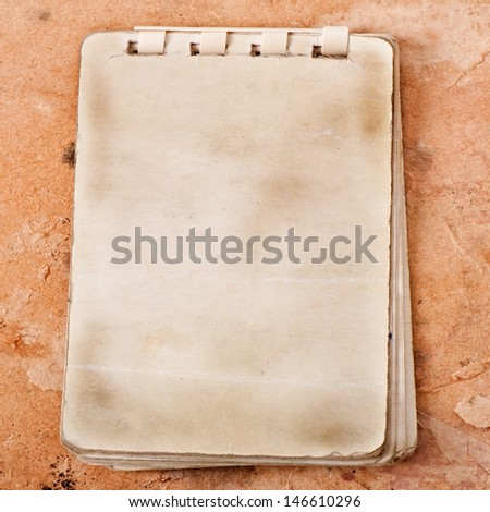 old notebook on the background of old paper - stock photo