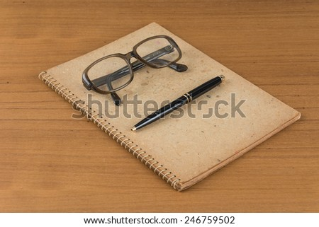 old notebook with pen and glasses on wood table - stock photo