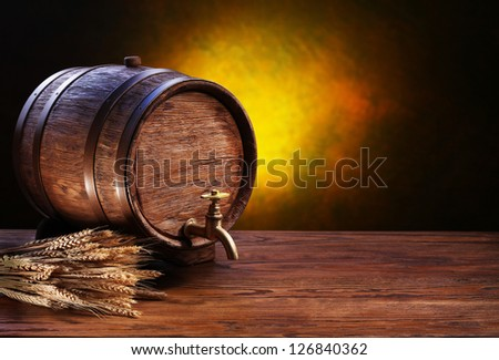 Old oak barrel on a wooden table. Behind blurred dark background.