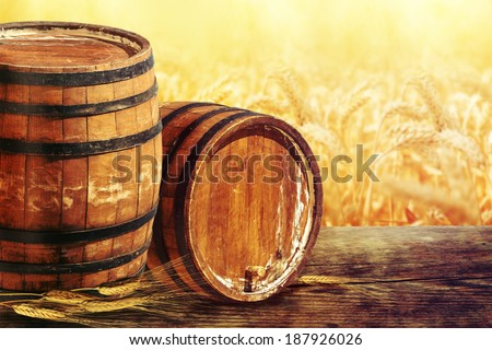 Old oak barrel on a wooden table on the wheat field background. - stock photo