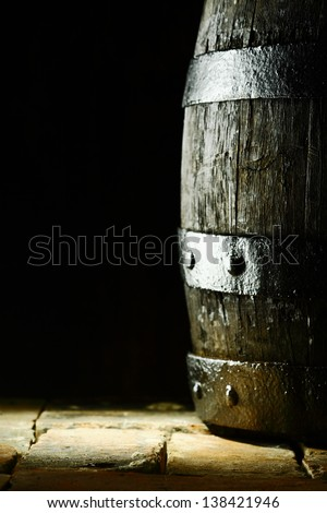 Old oak barrel standing upright on flagstones or old bricks with a dark background and copyspace conceptual of the aging and storing of wine, brandy or beer - stock photo
