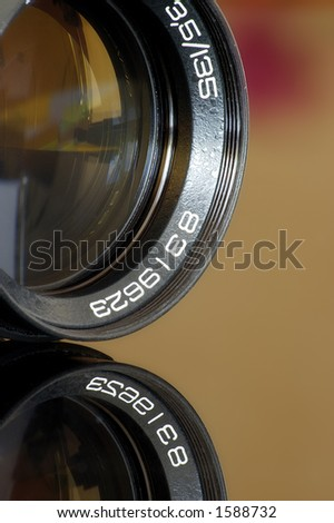 Old objective on glass with reflection - stock photo