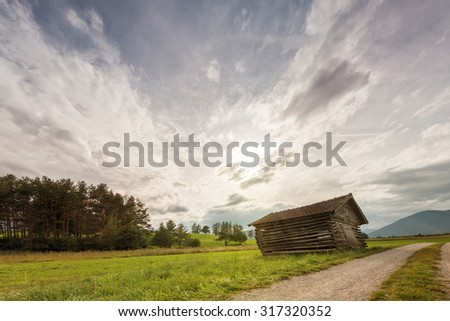 old oblique wooden shed house in meadow at dusk - stock photo