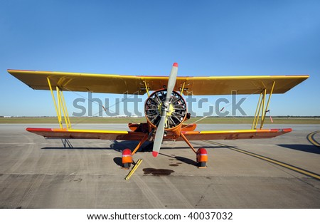 Old obsolete biplane parked on the ground - stock photo