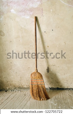 Old obsolete broom or besom leaning on the gray wall - stock photo