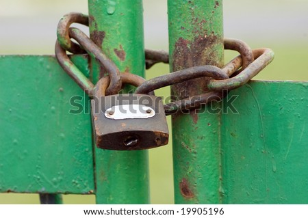 Old obsolete metal lock with chain green gate - stock photo