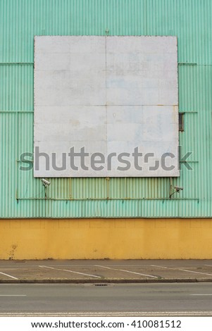 Old obsolete square shaped blank billboard surface as copy space mounted on wall - stock photo