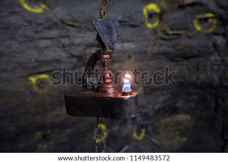Old oil  lamp with drilled dynamite holes in the background