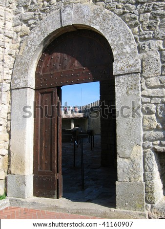 Old open arched wooden door set into an old gray stone wall - stock photo
