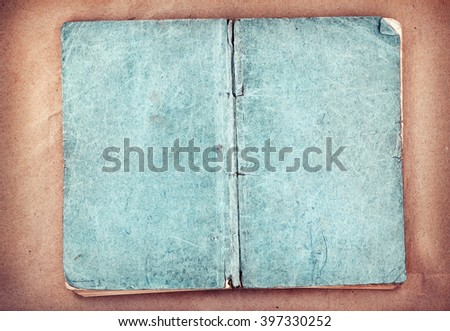 Old open book cover on brown paper background - stock photo