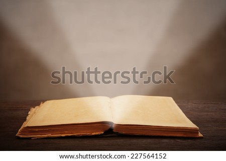 old open book lying on a wooden table light beam illuminates the page - stock photo