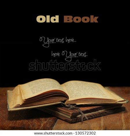 Old open book on a wooden table.