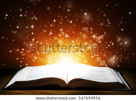Old open book with magic light and falling stars on wooden table - stock photo