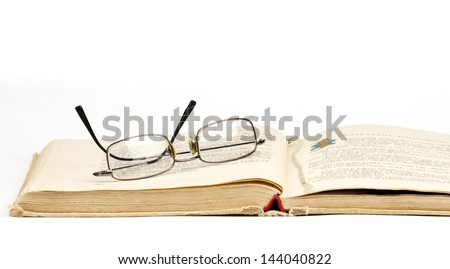 old open book with reading glasses isolated on white background with copy space - stock photo