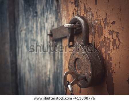 Old open padlock with key on a chain. Photo toned. - stock photo
