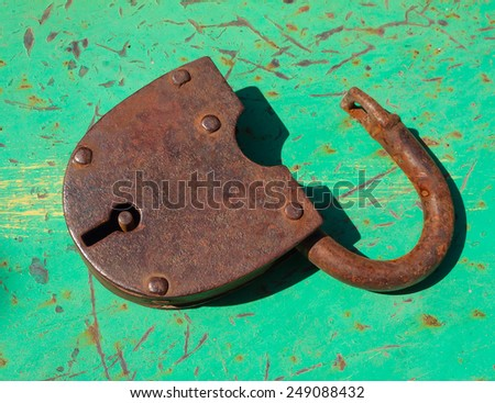 Old open rusty hinged door lock on an old painted surface - stock photo