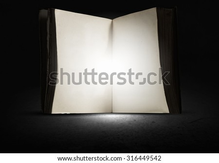 Old opened book with light coming from pages on dark background.