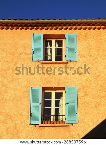 Old orange rural house with open windows and blue shutters, Provence, France. Sunny day - stock photo