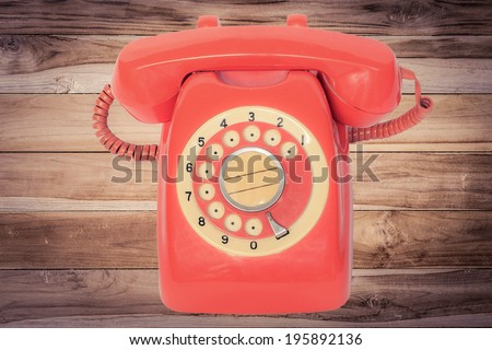 old orange telephone with rotary dial on wood in vintage tone - stock photo