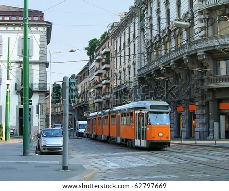 Old orange tram on the street of Milan, Italy - stock photo