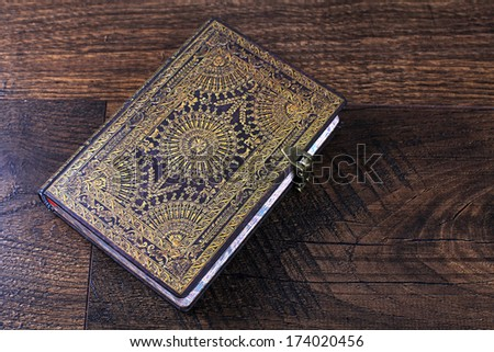 Old ornate notebook with leather stamped cover on antique wood background - stock photo