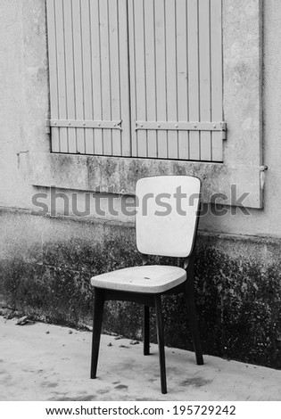 Old padded white leather chair standing near the window with closed wooden shutters outside of  the old house with stucco wall. Provence, France. Aged photo. Black and white. - stock photo