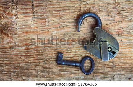 Old padlock and key on wood - stock photo
