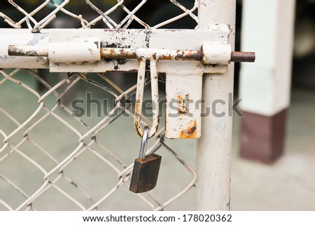 Old padlock and metal fence  with unlock - stock photo