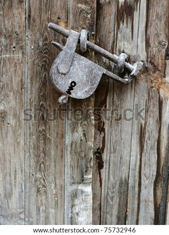 Old padlock on an old wooden door - stock photo