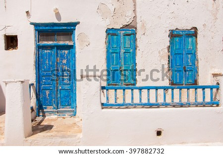 Old painted blue door and window on the whitewashed wall. Background. Typical for Greece... - stock photo