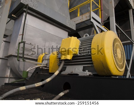 old, painted electric motor as drive exhaust fan - stock photo