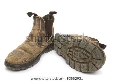 Old pair of dirty working boots on white background - stock photo