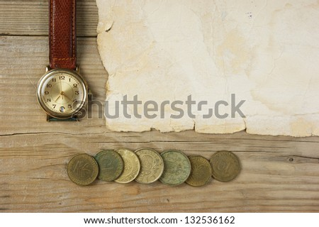 Old paper and coins on a wooden table
