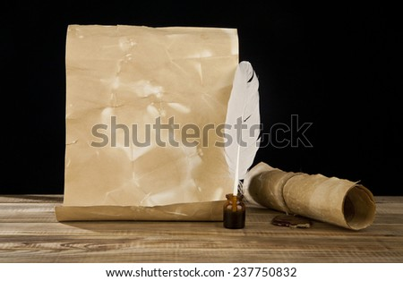 old paper and feather on a black background - stock photo
