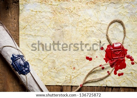 Old paper and scroll with the envelope symbol in sealing wax - stock photo