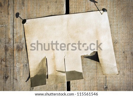 old paper announcement hanging on the wooden fence - stock photo
