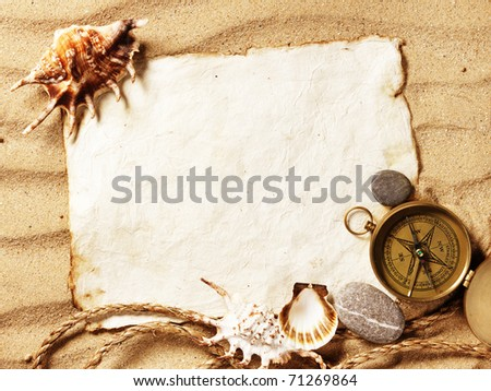 old paper, compass, shell and rope on sand background - stock photo
