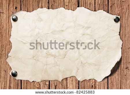 Old paper nailed to a wooden wall - stock photo