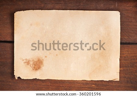 Old paper on a wooden background - stock photo