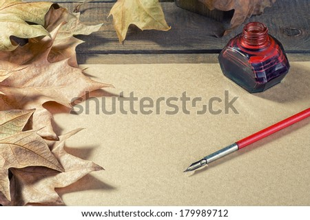 old paper pen fountain, foliage, inks on a wooden table - stock photo