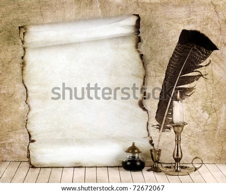 Old paper with a candle and a quill pen. - stock photo