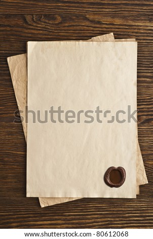 old paper with a wax seal on a wooden background - stock photo