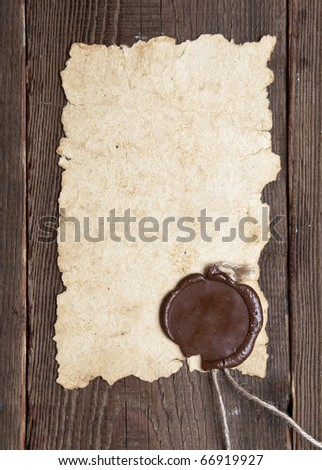 old paper with a wax seal on brown wood texture with natural patterns - stock photo